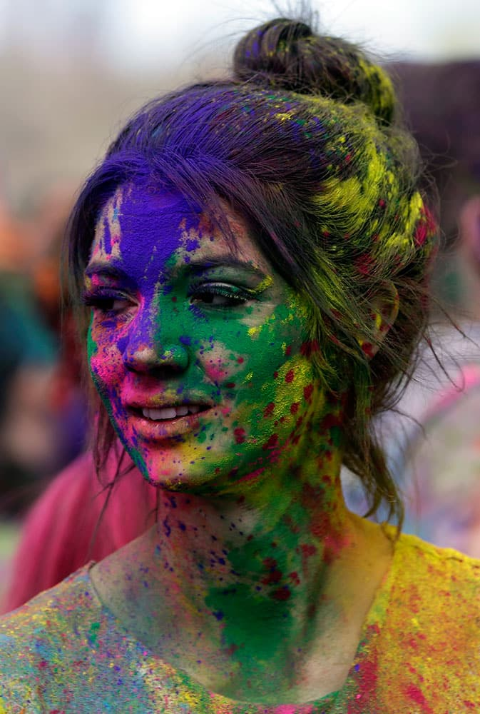 A reveler covered in colored corn starched looks on during the 2015 Festival of Colors, Holi Celebration at the Krishna Temple, in Spanish Fork, Utah.