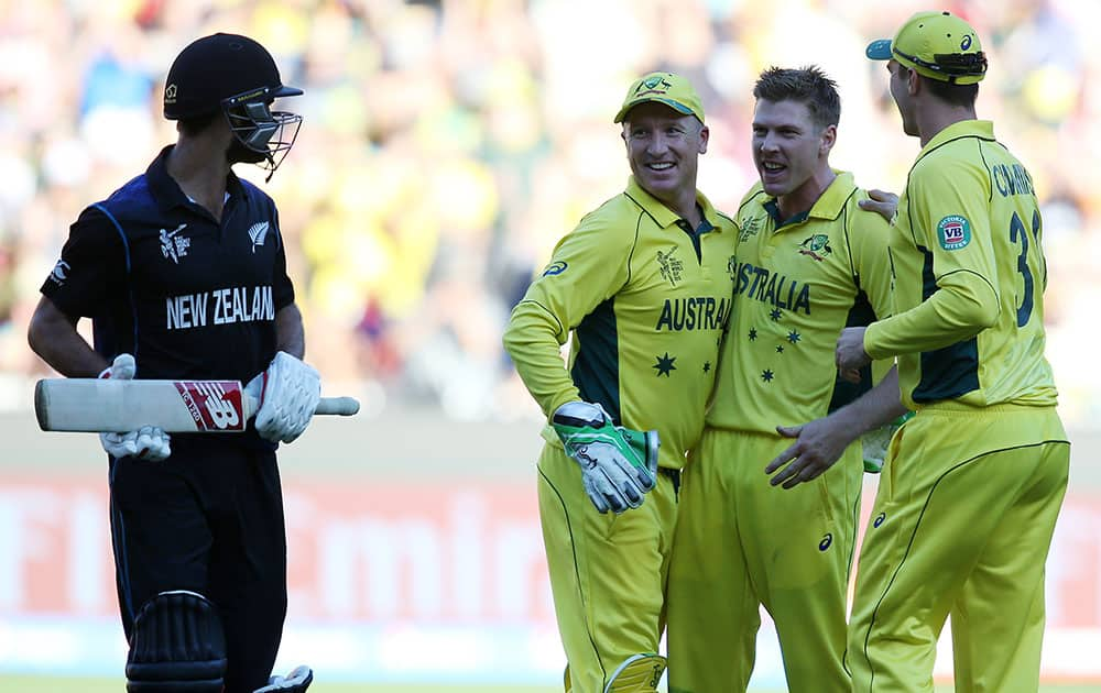 New Zealand's Grant Elliott, left, chats with Australian players Brad Haddin, second left, and James Faulkner as Pat Cummins, right, celebrates after he was dismissed for 83 runs during the Cricket World Cup final in Melbourne, Australia.