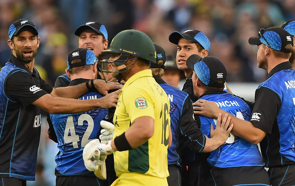 New Zealan's cricketers watch Australia's Aaron Finch walk off the field after being dismissed during the ICC Cricket World Cup final in Melbourne, Australia.