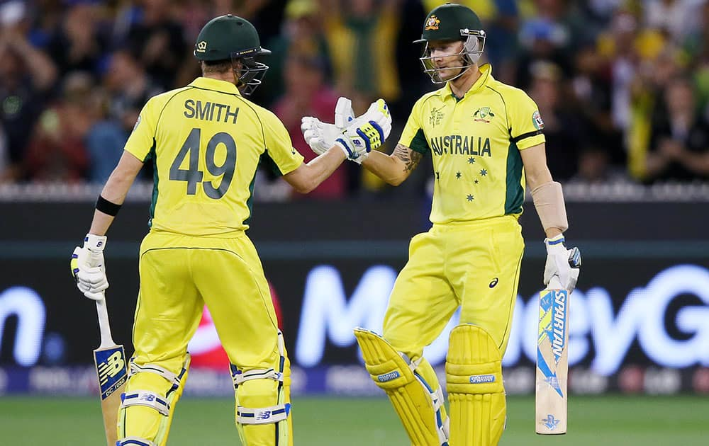 Australian captain Michael Clarke, right, is congratulated by teammate Steve Smith after scoring 50 runs while batting against New Zealand during the Cricket World Cup final in Melbourne, Australia.