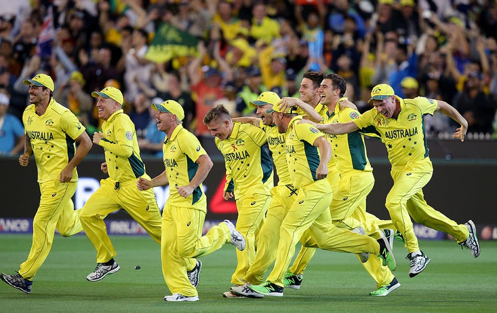 Australian players celebrate after they defeated New Zealand by seven wickets to win the Cricket World Cup final in Melbourne, Australia.