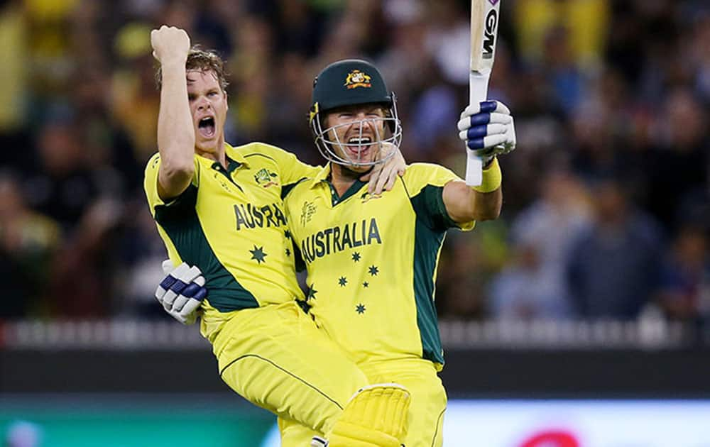 Australia's Steve Smith, left, and teammate Shane Watson celebrate after defeating New Zealand by seven wickets to win the Cricket World Cup final in Melbourne, Australia.