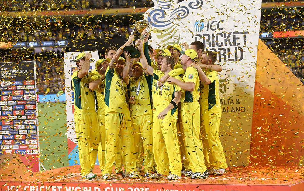 Australian captain Michael Clarke holds the trophy aloft with his teammates as they celebrate their seven wicket win over New Zealand in the Cricket World Cup final in Melbourne, Australia.