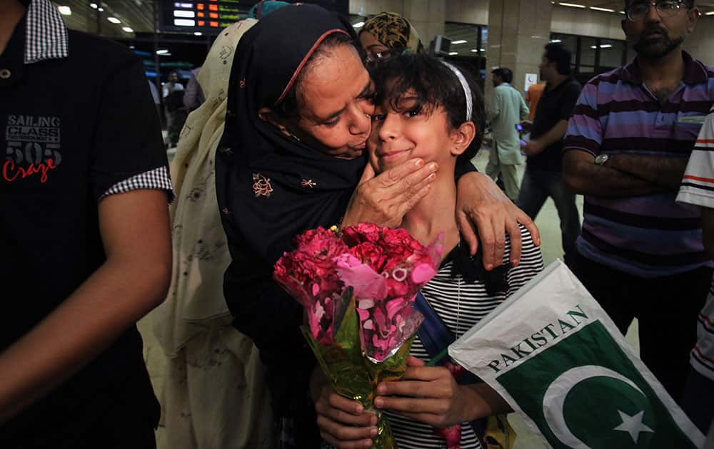 A Pakistan girl, who with her family members evacuated from Yemen, is greeted by her relatives upon their family arrival in Jinnah International Airport in Karachi, Pakistan.
