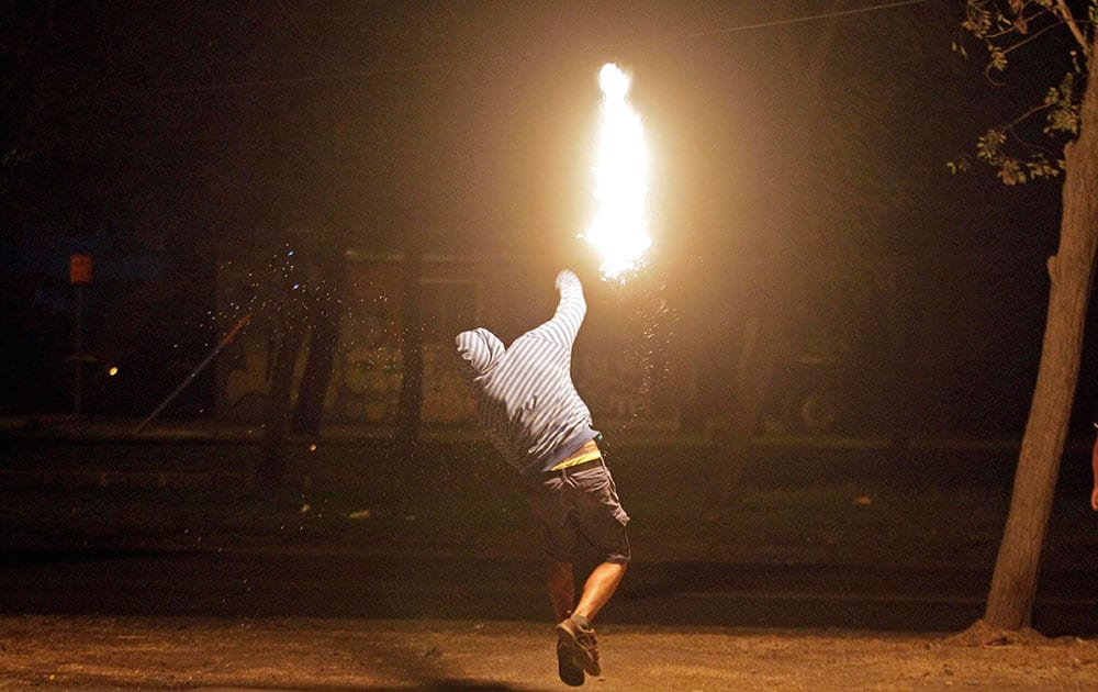 A masked man throws a petrol bomb at police during a manifestation, commemorating the 30th anniversary of the Day of the Young Fighter, that marks the deaths of two brothers who were members of an anti-government group, in Santiago, Chile.
