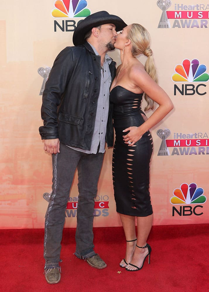 Jason Aldean, left, and Brittany Kerr arrive at the iHeartRadio Music Awards at The Shrine Auditorium, in Los Angeles.