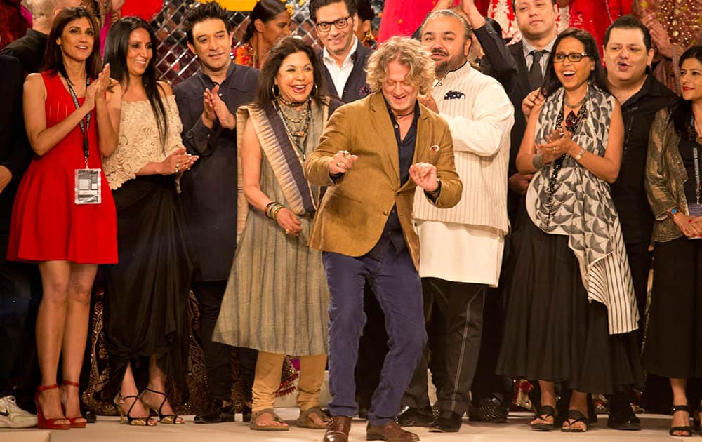 Indian designer Rohit Bal, center, dances as other designers watch during the grand finale of Amazon India fashion Week.