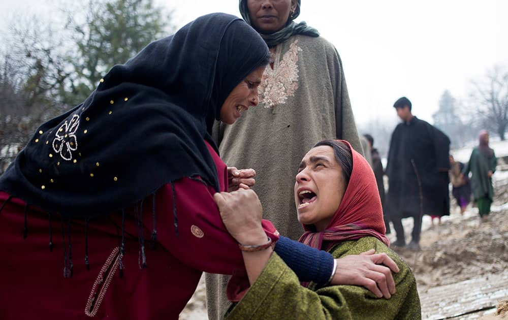 An unidentified woman, left, comforts a relative of landslide victims in village of Laden some 45 Kilometers (28 miles) west of Srinagar, India.