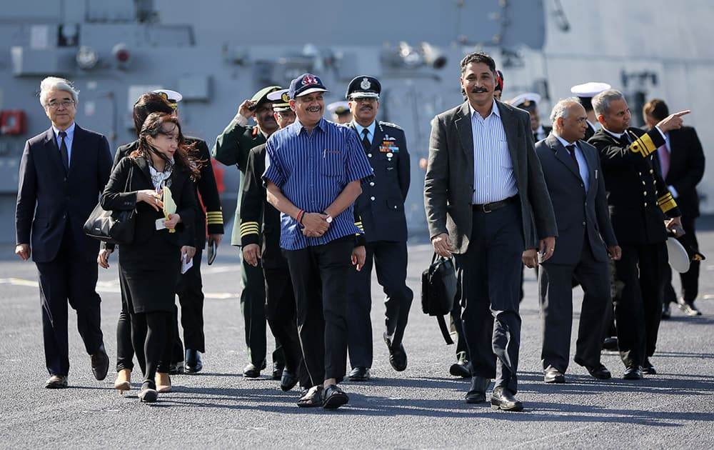 Defense Minister Manohar Parrikar, in a blue shirt, is guided on the flight deck of the latest destroyer Izumo of Japan's Maritime Self-Defense Force (JMSDF) in Yokosuka, south of Tokyo.