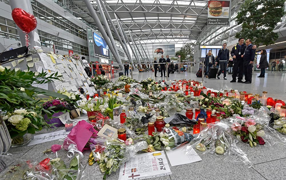 Passengers watch candles and flowers for the victims of the plane crash at the airport in Dusseldorf , Germany.