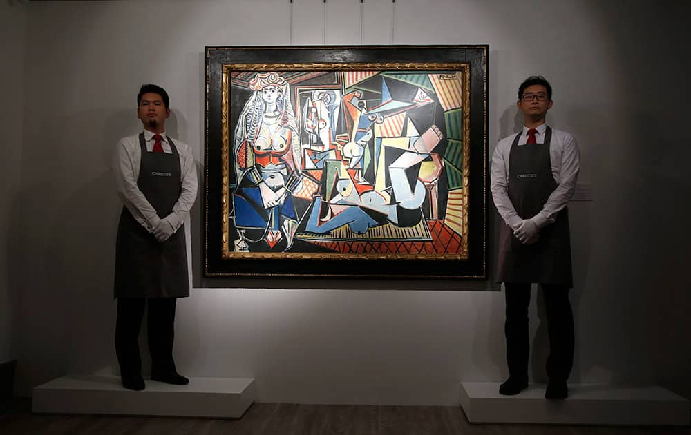 Staff members from Christie's auction house stand next to the painting 'Les Femmes d'Alger (Version