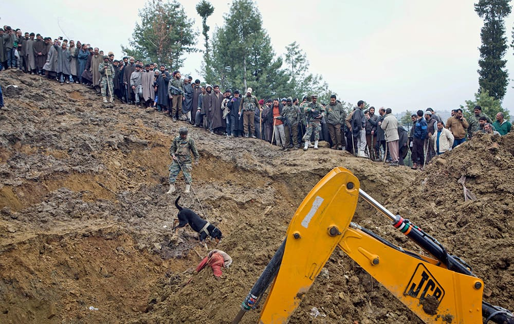 An Indian army sniffer dog looks for a missing boy after a landslide caused by the recent floods in the village of Laden, some 45 kilometers (28 miles) west of Srinagar, Kashmir.