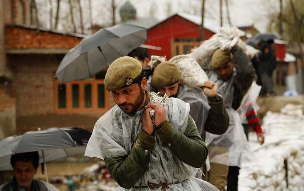 Jammu and Kashmir policemen carry sand bags to repair a breach in an embankment in a flooded area of Srinagar, Kashmir.