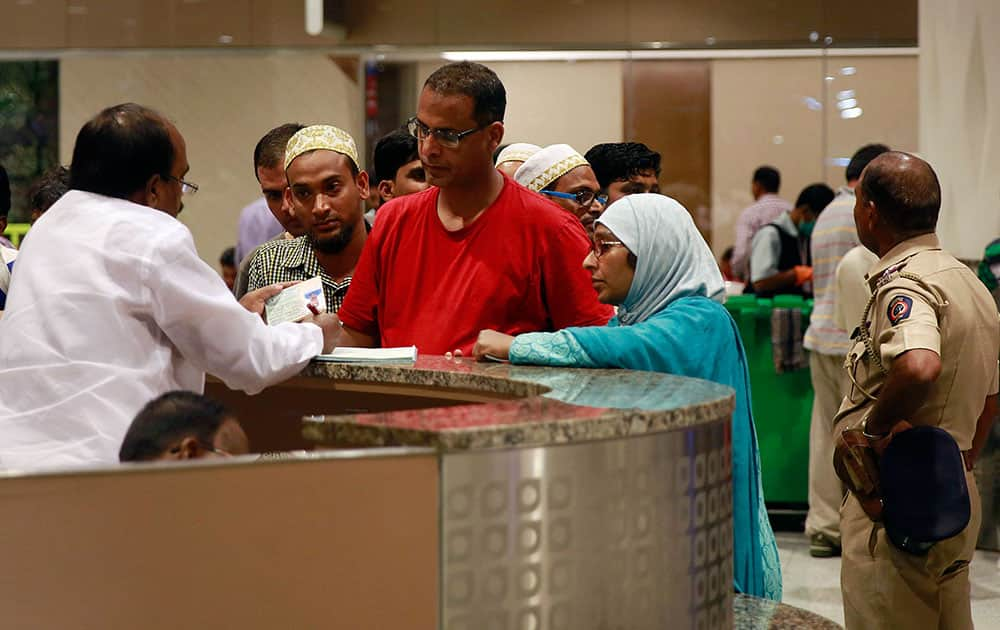 An Indian official checks the paper of Indians who were evacuated from Yemen after arriving at Chhatrapati Shivaji International Airport in Mumbai.