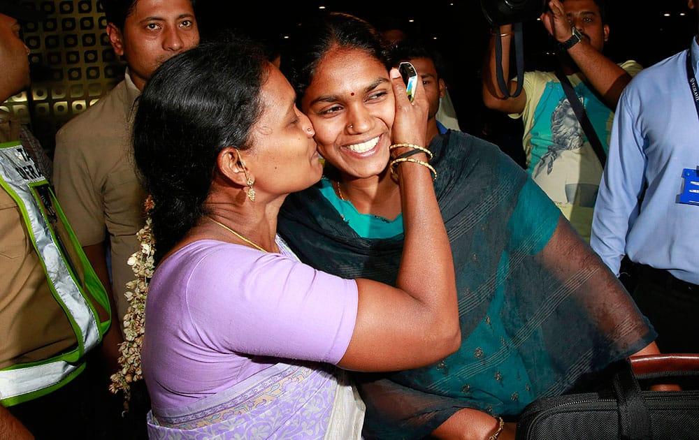 A woman greets her relative who arrived at Chhatrapati Shivaji International Airport in Mumbai.
