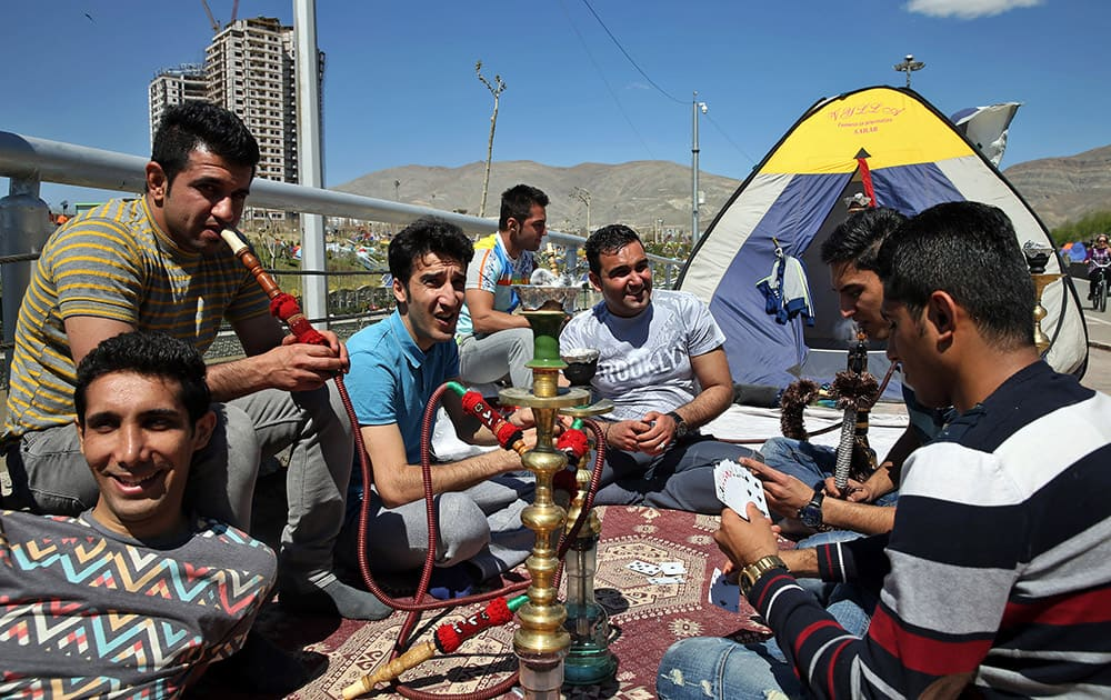 Two Iranian men smoke a water pipe as others play cards while spending their time outdoors observing the ancient festival of Sizdeh Bedar, an annual public picnic day on the 13th day of the Iranian new year, a legacy from pre-Islamic era, in the last day of Persian New Year holiday at the Pardisan Park in Tehran, Iran.