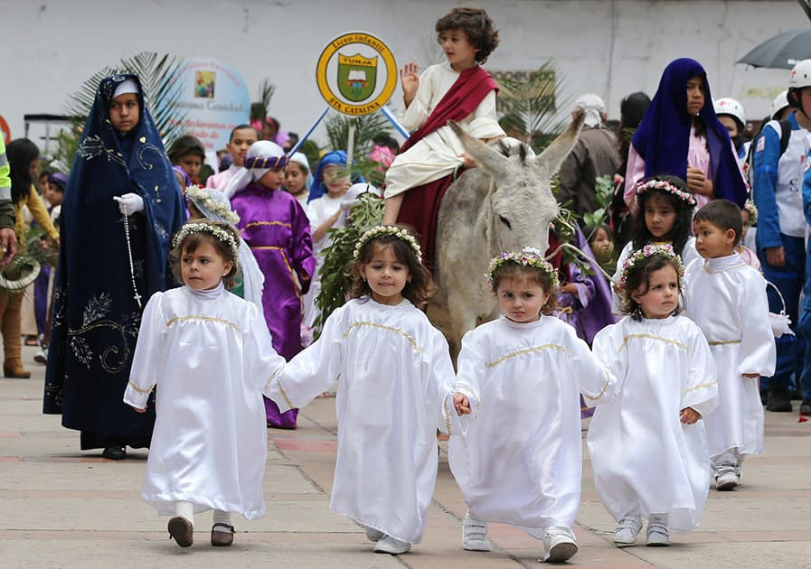 Children dressed as angels lead a boy portraying Jesus Christ and his triumphant return to Jerusalem, in the Children's Holy Thursday Procession, in Tunja, Colombia.