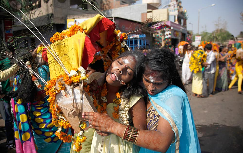 A woman tries to control a devotee in trance with her tongue pierced with a metal rod, on her way to a temple of Lord Murugan, on the occasion of Panguni Uthiram festival, in Ahmedabad.