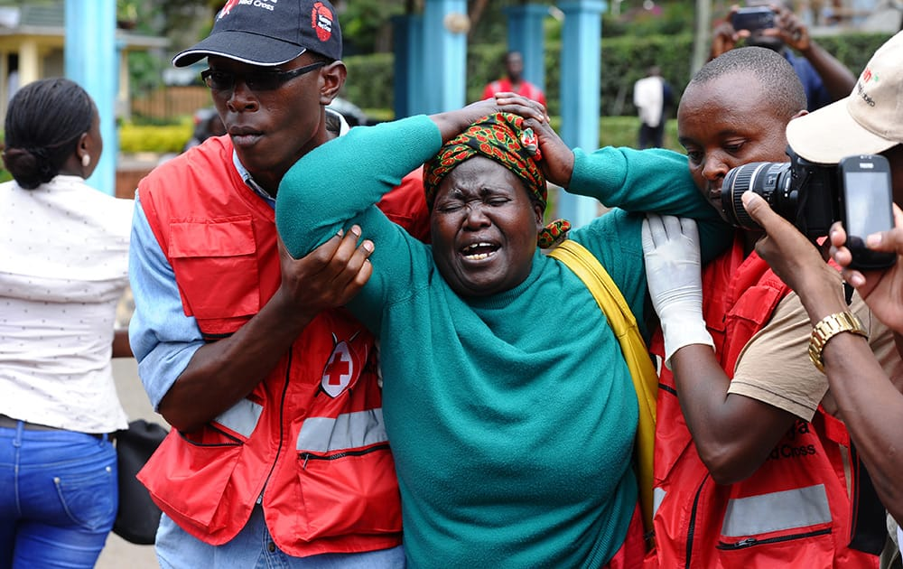 Kenya Red Cross staff assist a woman after she viewed the body of a relative killed in Thursday's attack on a university, at Chiromo funeral home, Nairobi, Kenya.