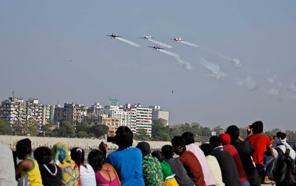 People watch as aircrafts of the British aerobatics team Global Stars perform during the third day of an air show in Ahmadabad.