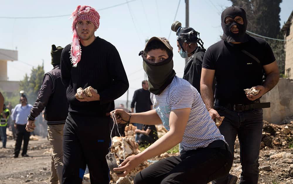 Palestinian protestors prepare to throw stones at Israeli troops during clashes following a protest against the nearby Jewish settlement of Kdumim in the West Bank village of Kufr Qaddum.