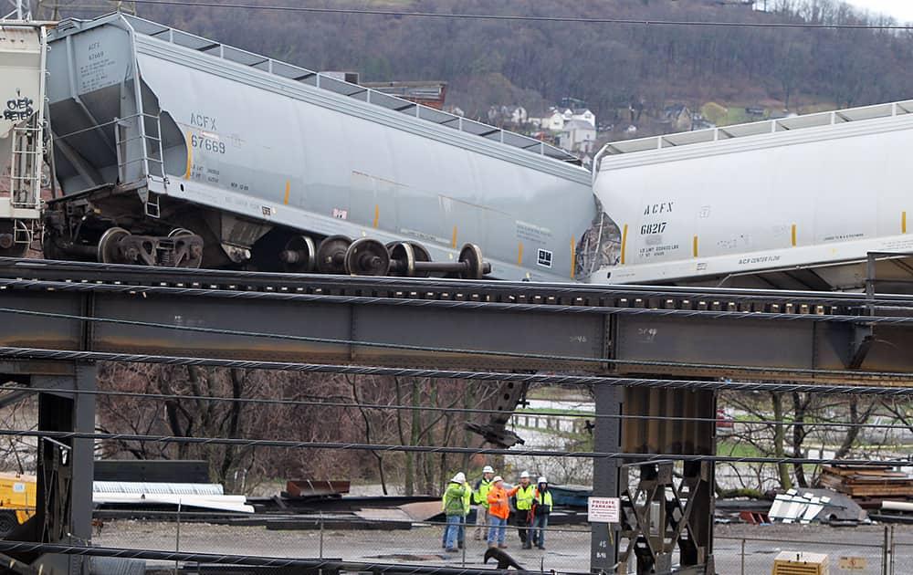 Workers look over the train derailment on elevated tracks, in Cincinnati.