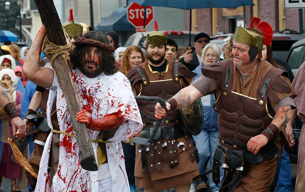 A volunteer from the Bridgewater Community Churches portraying a Roman Centurion, whips the man portraying Jesus as they perform a reenactment of the crucifixion of Jesus on Good Friday, in Bridgewater, Pa.
