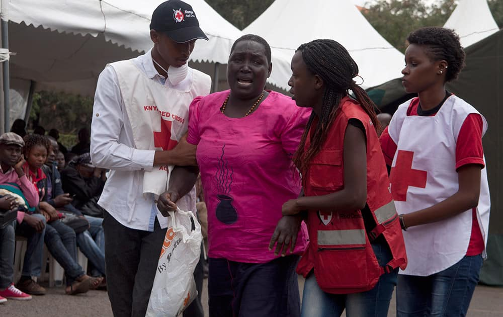 Red Cross staff console a woman after she viewed the body of a relative killed in Thursday's attack on a university, at Chiromo funeral home, Nairobi, Kenya.