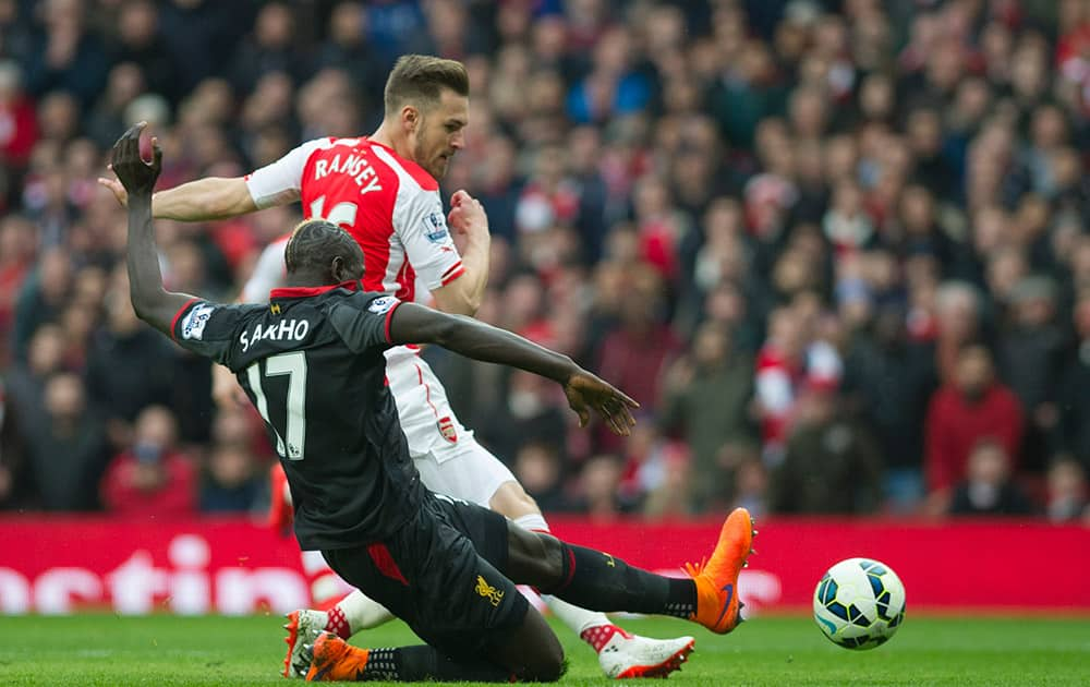 Arsenal's Aaron Ramsey tries to score past Liverpool's Mamadou Sakho during their English Premier League soccer match at Emirates Stadium, in London.
