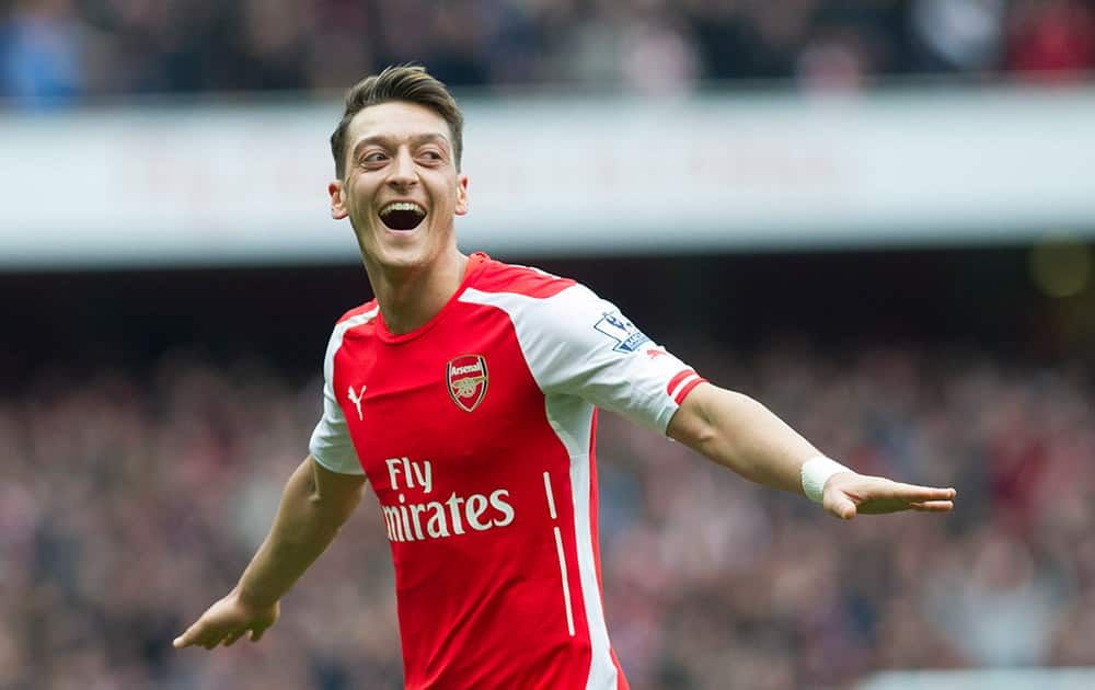 Arsenal's Mesut Özil celebrates after scoring against Liverpool during their English Premier League soccer match at Emirates Stadium, in London.