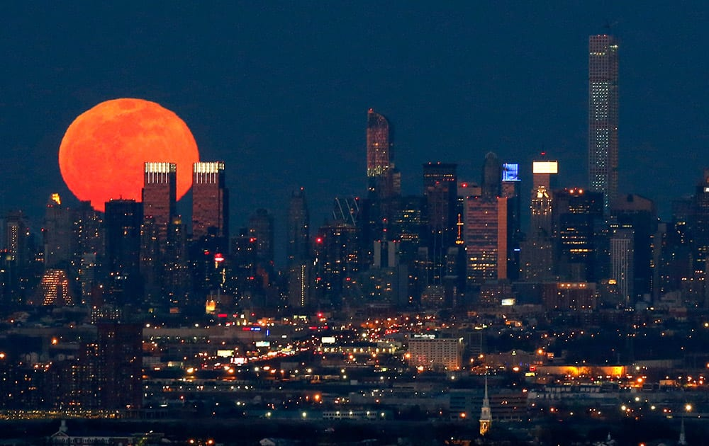 A full moon is seen as it rises over the New York City skyline seen from West Orange, N.J.