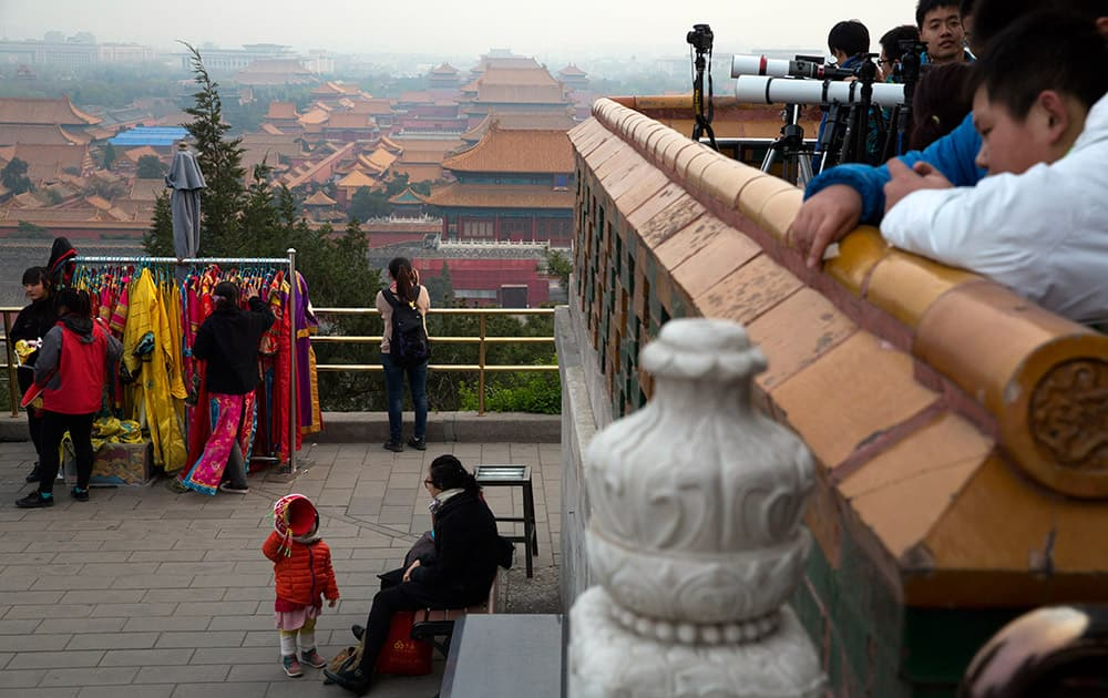 A child plays with a hat as students from an astronomy club wait with telescopes to view a lunar eclipse from a hilltop pavilion in Beijing.