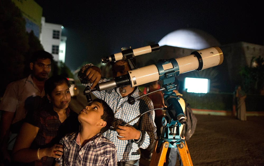 A school student looks into a telescope to watch a lunar eclipse outside a planetarium in Guwahati.