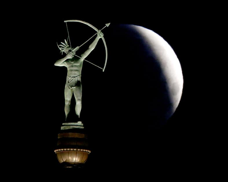 A partially eclipsed full moon sets behind a statue of a Kansa Indian at the Kansas Statehouse, in Topeka, Kan.