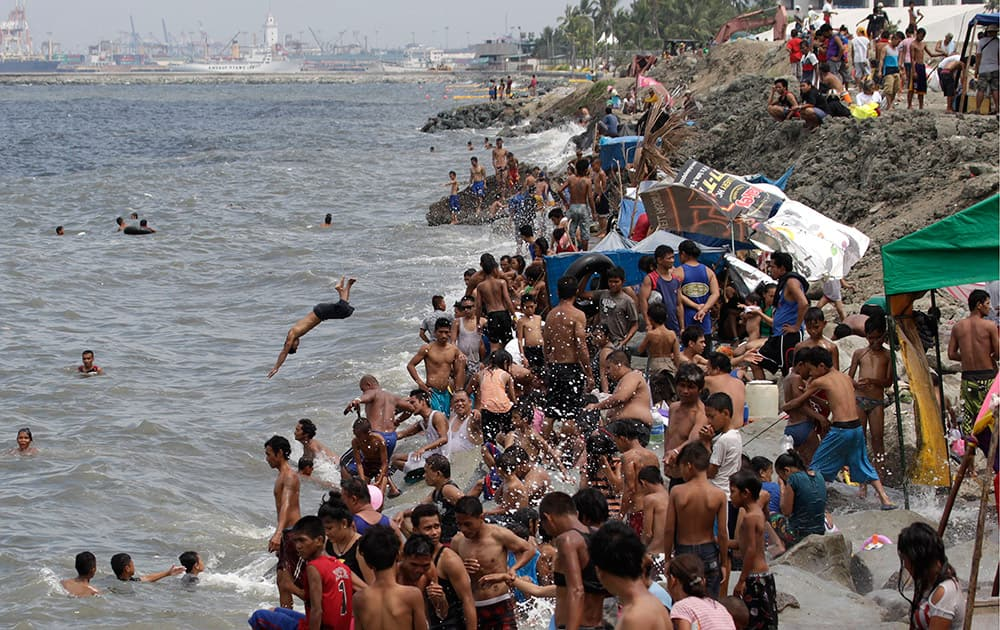 Filipinos swim in the polluted waters of Manila's bay, Philippines as they celebrate Easter.