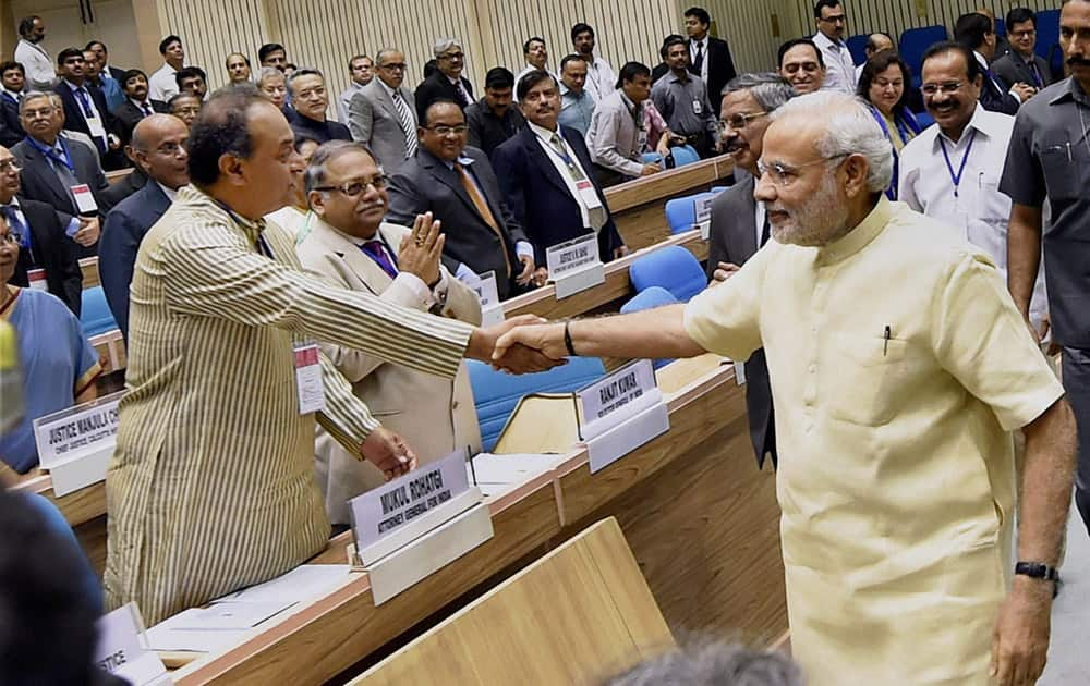 Prime Minister Narendra Modi shakes hand with Attorney General of India Mukul Rohatgi during the inauguration of the joint conference of the CMs and the CJs of High Courts at Vigyan Bhawan in New Delhi.