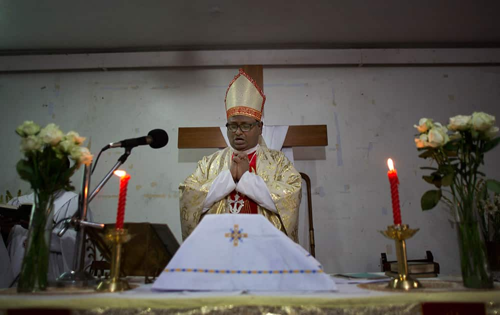 A Christian priest prays during Easter mass at a Church in Guwahati.