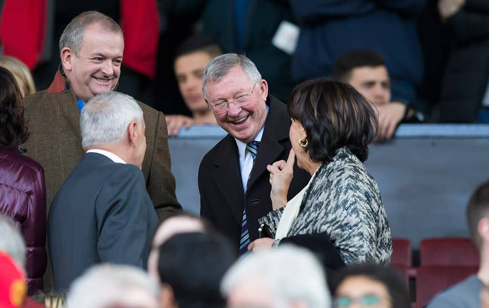 Manchester United's former manager Alex Ferguson, centre, laughs as he takes his seat before the English Premier League soccer match between Manchester United and Aston Villa at Old Trafford Stadium, Manchester, England.