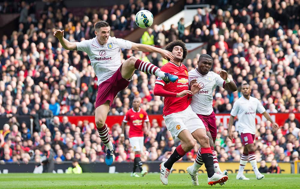 Aston Villa's Ciaran Clark, left, clears the ball away from Manchester United's Marouane Fellaini as Jores Okore looks on during the English Premier League soccer match between Manchester United and Aston Villa at Old Trafford Stadium, Manchester, England.