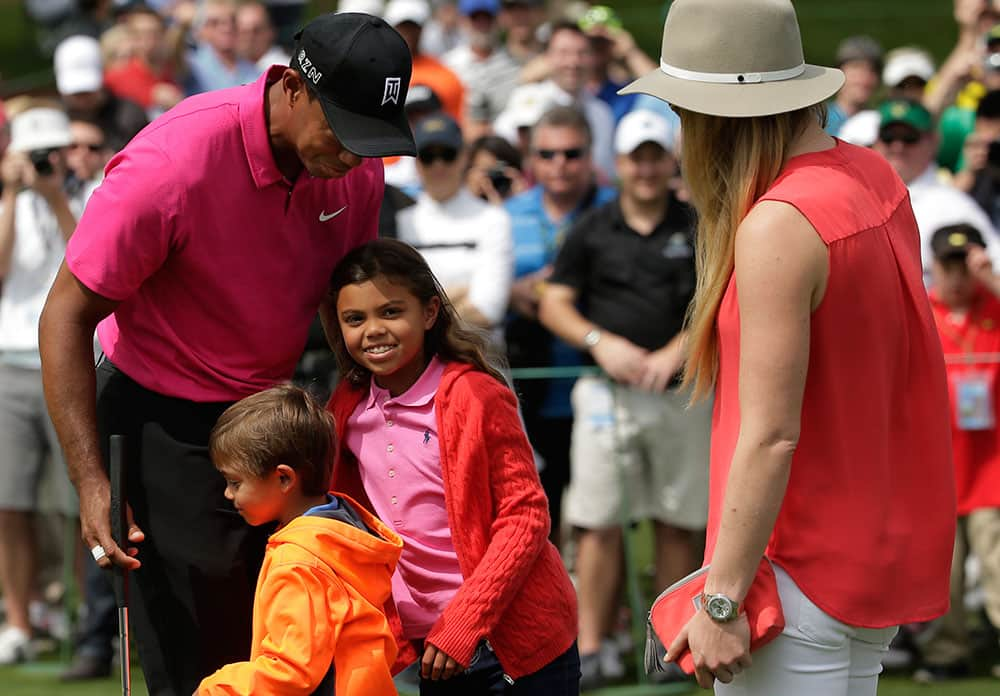 Lindsey Vonn watches as Tiger Woods hugs his children Charlie and Sam during a practice round for the Masters golf tournament, in Augusta, Ga.