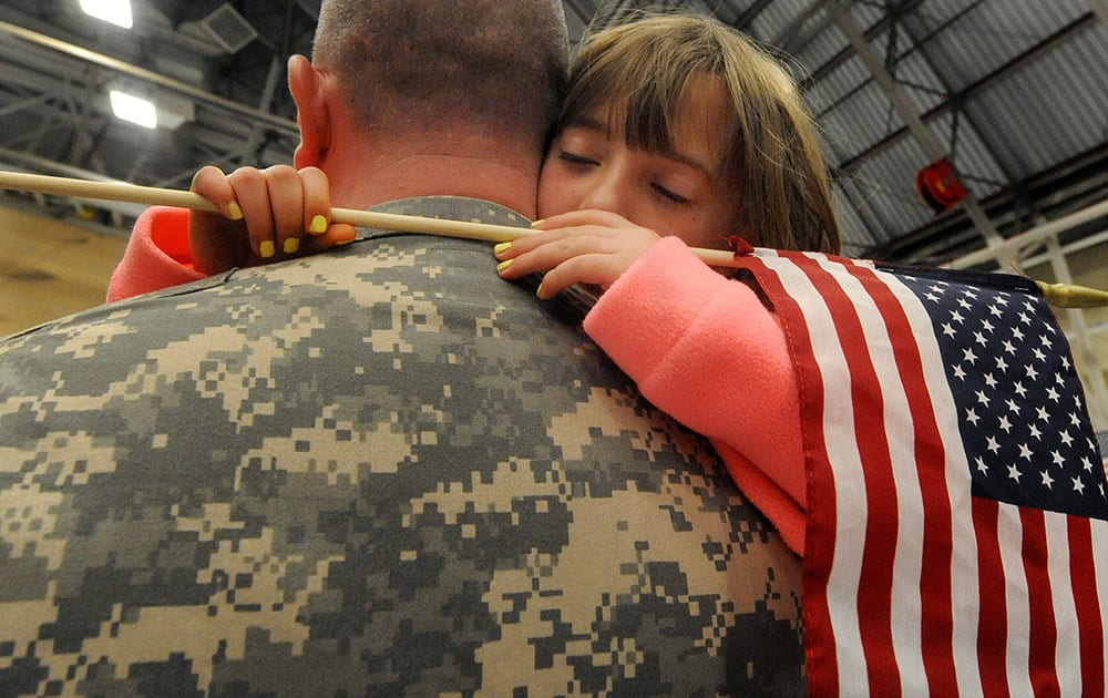 Ashley Nowakowski, 8, of Colchester Conn., hugs her father Major Stephan Nowakowski, during a deployment send off ceremony at the Connecticut National Guard base, in Windsor Locks, Conn.