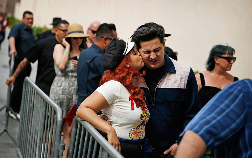 Angie Almilla kisses Eric Martinez while waiting in line for a pool party at the Viva Las Vegas Rockabilly Weekend in Las Vegas.