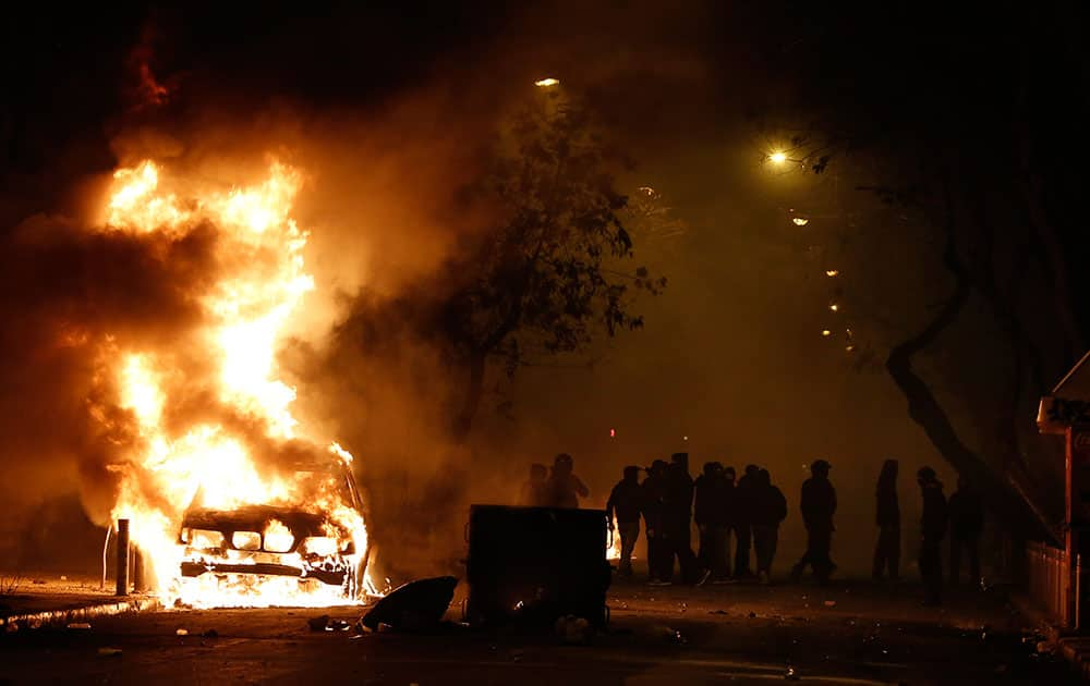 Rioting youths stands next to a car on fire during clashes after a demonstration by about 700 anarchists seeking the abolition of a maximum security prison, in central Athens.