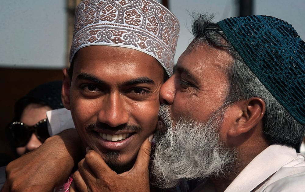 A Pakistani boy, evacuated from Yemen by Pakistan Navy ship, is kissed by his father upon his arrival at Karachi port in Pakistan.
