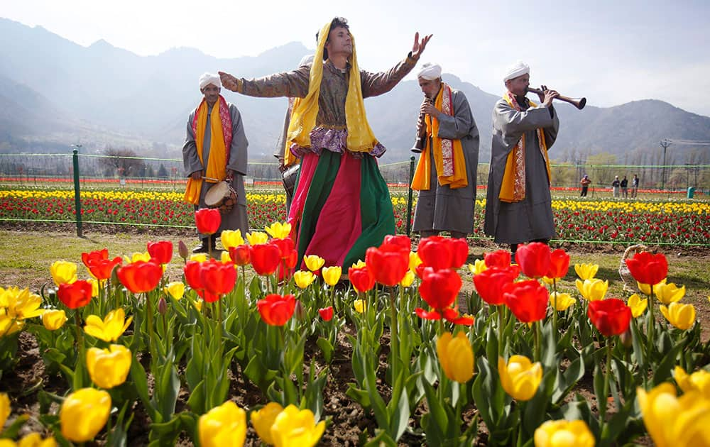 Kashmiri traditional folk dancers perform during the season's opening of Siraj Bagh, claimed to be the largest tulip garden in Asia, on Zabarwan Hills in Srinagar.