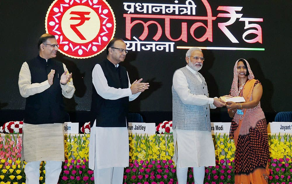 Prime Minister Narendra Modi hands over a cheque as Union Minister for Finance Arun Jaitley and MoS for Finance, Jayant Sinha look on at the launch of Pradhan Mantri MUDRA (Micro Units Development and Refinance Agency) Yojana in New Delhi.