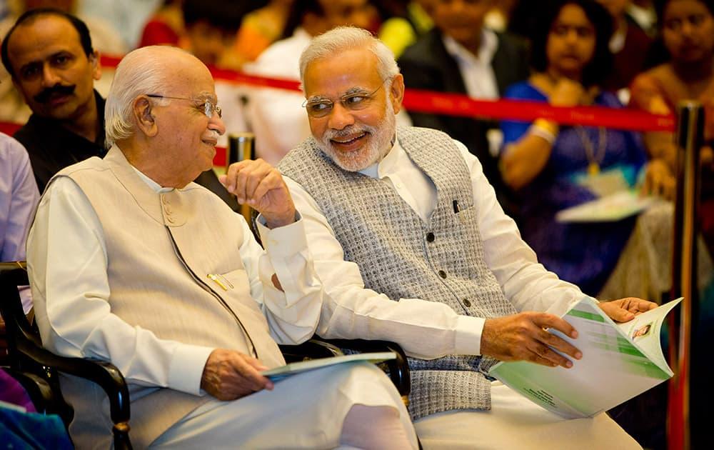 Prime Minister Narendra Modi, speaks with Bharatiya Janata Party senior leader L.K.Advani during a civil investiture ceremony at the presidential palace in New Delhi.