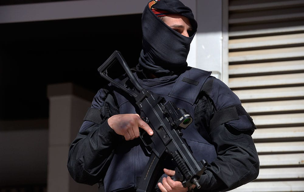 A Mossos d'Esquadra regional police officer stands guard during a raid in one of the region's biggest operations against jihadi activity in Sabadell, near Barcelona, Spain.