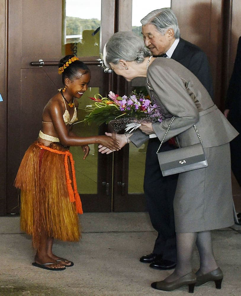 Japanese Emperor Akihito and Empress Michiko smile as they are greeted by a Palauan girl with a welcome bouquet upon their arrival at Palau International Airport on the outskirts of Koror in Palau.