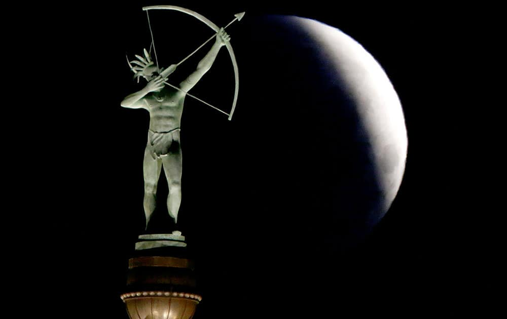 A partially-eclipsed full moon sets behind a statue of a Kansa Indian at the Kansas Statehouse, in Topeka, Kan.